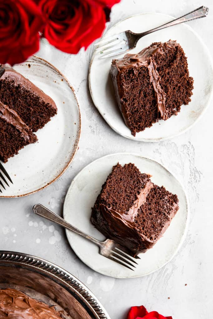 several slices of Dairy Free Chocolate Cake on plates with forks