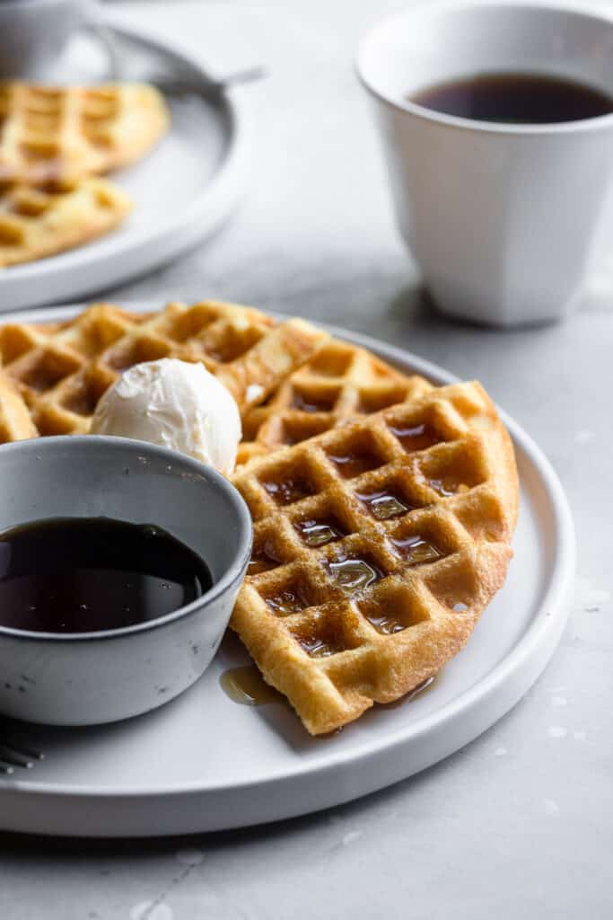 Dairy Free Waffles on a plate with a side of syrup