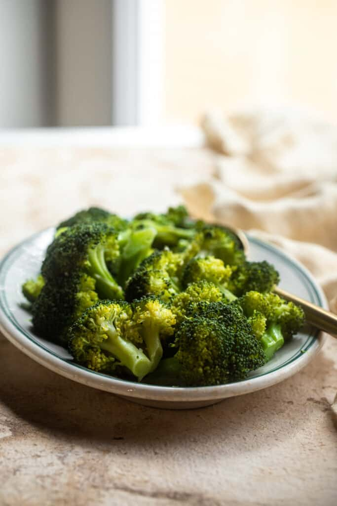 Instant Pot Steamed Broccoli on a serving plate with a fork