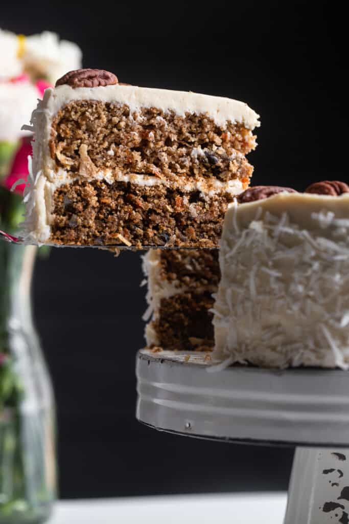 Low Carb Keto Carrot Cake on a cake stand with a piece being lifted out