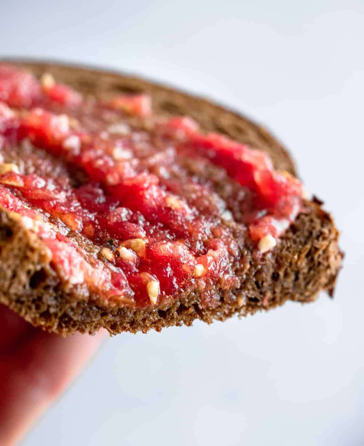 close up of hand holding pan con tomate
